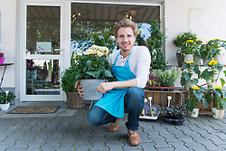 Portrait of mid adult man holding potted plant of flower, smiling