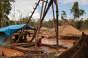 A miner controls a machine built to suck and expel mud from a hole in the jungle, this mud carries gold that after a day's work is collected with carpets.