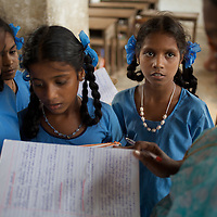 Anjalakshi Krishnamurthy (age 10, wearing white beads) looks at her teacher attending class at the Government Girls High School, Venugopalapuram in Cuddalore. ..The five Krishnamurthy sisters from Pudupettai were placed in the Government Home for Tsunami Children in Cuddalore, Tamil Nadu when they lost their mother to the 2004 tsunami. Their father, Krishnamurthy, had decided he could no longer provide day-to-day care for his daughters. Krishnamurthy later remarried. The Krishnamurthy sisters now range in age from eight to sixteen...The four younger sisters are still at the Governement home (or orphanage). In summer 2009, Sivaranjini, the eldest aged sixteen, failed her 10th Standard exams and had to drop out of school so leaving her not eligible for care at the Government home. She is now living with her father and his new wife Nagamalli's house 30km away in Pudupettai. Krishnamurthy is intending that Sivaranjini marry a second cousin in 2010. ..Krishnamurthy visits the Government orphanage once a week to see his four younger daughters. Nagamalli is popular with all five sisters. She provides them attention when they are together and is genuinely interested in their well-being. Sivapriya remains close to her paternal aunt Kamasala with whom she used to live in the fishing village of Thazanguda. Kamasala visits Sivapriya at the orphanage every fortnight. The sisters return to their father's home for festivals including Diwali and the Pudupettai village temple festival...According to Revathi, the staff member in charge at the Government home, the absence of the elder Sivaranjini has had the effect of making the remaining four sisters still at the home increasingly independent. For instance, where they used to all sleep together the girls now sleep in different dormitories. The eldest of these four, fourteen year-old Sivapriya has adopted some of the responsibilities of her elder sisters including coordinating clothes washing and helping her younger siblings with scho