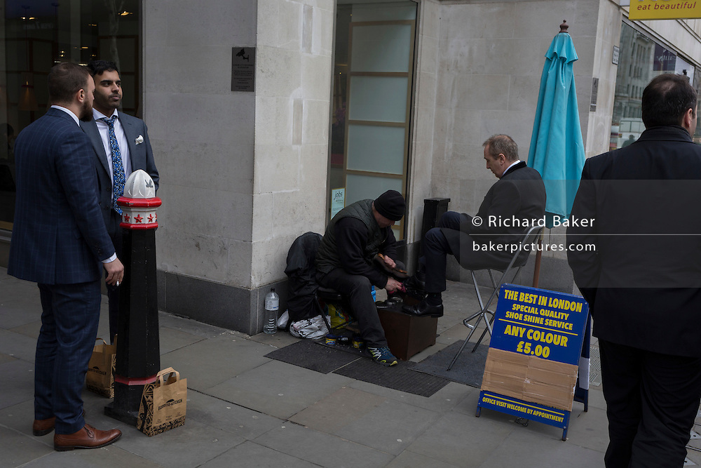 A shoe shiner polishes the shoes of a customer, with others waiting in the street, on 16th February 2017, in the City of London, England.