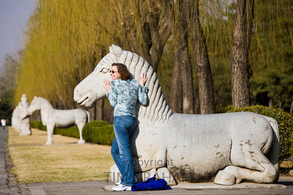 Tourist poses with statue of a resting horse, Spirit Way, Ming Tombs, Changling, Beijing, China