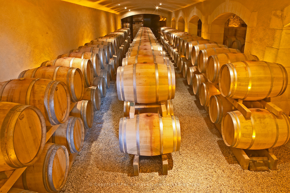 The barrel ageing cellar with rows and stacks of oak barriques Chateau Thieuley La Sauve Majeure Entre-deux-Mers Bordeaux Gironde Aquitaine France