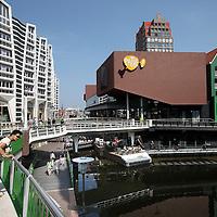 Nederland, Zaandam , 6 juli 2013.<br /> Wandeling door de binnenstad van Zaandam.<br /> Starten bij De Werf aan de Oostzijde. Daarvandaan kun je lopen op een soort boulevard tussen de flats en het water. De eerste stop is De Fabriek, filmhuis en eetcafé met terras aan de Zaan met uitzicht op de sluis. Daarna de sluis zelf.<br /> Dan langs het winkelgebied richting de Koekfabriek: Het oude Verkade pand dat is verbouwd en waar nu de bieb en sportschool en restaurant etc. in zitten.<br /> (Dat is aan de overkant van het startpunt) en misschien nog de Zwaardemaker meepakken aan de Oostzijde. Dat is een oud pakhuis die Rochdale enige jaren geleden heeft verbouwt tot appartementen met een stukje Nieuwbouw.<br /> Ook doen: het Russische buurtje vlakbij de Zaan. Dit jaar staat Rusland in de schijnwerpers en Zaandam heeft een speciale band met Rusland, vanwege het Czaar Peterhuisje en de Russische buurt. <br /> Op de foto: Het nieuwe winkelcentrum met veel vernieuwde Zaanse stijl in de architectuur. Op de achtergrond het appartementengebouw de Tsaar van Sjoerd Soeters dat uittorent boven de Russische buurt onderdeel van project.<br /> Foto:Jean-Pierre Jans