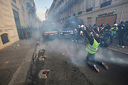 December, 8th, 2018 - Paris, Ile-de-France, France: Demonstrator kneeling on ground, arguing with riot police on Champs Elysees. The French 'Gilets Jaunes' demonstrate a fourth day. Their movement was born against French President Macron's high fuel increases. They have been joined en mass by students and trade unionists unhappy with Macron's policies. Nigel Dickinson