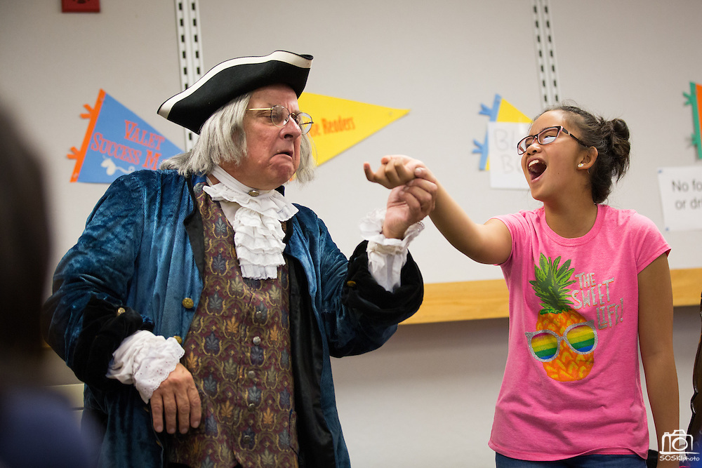 Ben Franklin (played by Phil Soinski) inspects 10-year-old Guiliana Samonte's finger during the International Printing Museum's Ben Franklin's Colonial Assembly: A Museum On Wheels at Curtner Elementary School in Milpitas, California, on May 13, 2014. (Stan Olszewski/SOSKIphoto)