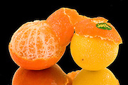 Close up of a freshly citrus fruit one tangerine partially peeled and one lemon on black background