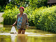 30 SEPTEMBER 2016 - SAI NOI, AYUTTHAYA, THAILAND: A woman walks through flooded streets back to her home in Sai Noi. The Chao Phraya River, the largest river that runs through central Thailand, has hit flood stage in several areas in Ayutthaya and Ang Thong provinces. Villages along the river are flooded and farms are losing their crops due to the flood. This is the same area that was devastated by floods in 2011, but the floods this year are not expected to be as severe. The floods are being fed by water released from upstream dams. The water is being released to make room for heavy rains expected in October.      PHOTO BY JACK KURTZ