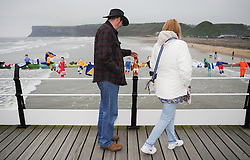 © Licensed to London News Pictures. <br /> 24/05/2014. <br /> <br /> Saltburn, United Kingdom.<br /> <br /> A couple pause to look at some of the World Cup themed knitted figures that appeared overnight on the pier in Saltburn.<br /> <br /> The Saltburn Yarn Stormers, a secret group of knitters based around the town have struck once again and produced their latest work in the build up to the World Cup by creating knitted figures representing the countries taking part in the World Cup in Brazil later in the year.<br /> <br /> The identities of the group members which remains a secret launched their most recent creation in the early hours to avoid possible detection and secretly gathered to attach the figures to the railings on the Victorian pier in the town before melting away back in to the shadows.<br /> <br /> Photo credit : Ian Forsyth/LNP