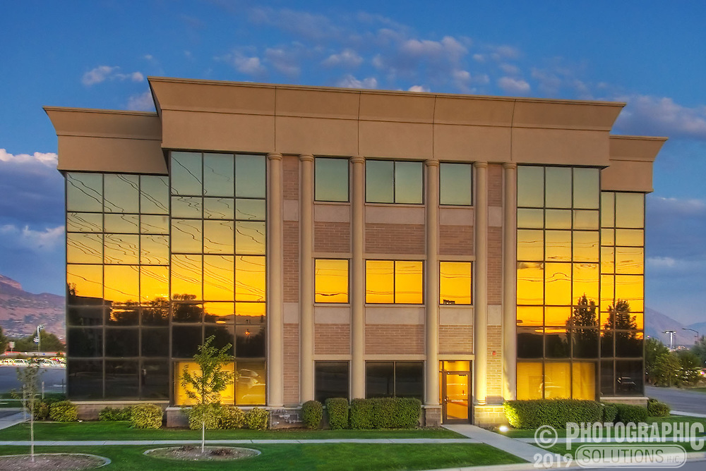 The sunset reflecting off the golden tinted windows of an office building