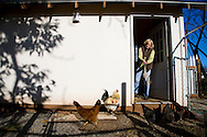 Sheryl and Dan Hall's historic Oregon City home, the White Kellogg House, an 1845 classic revival home set on 8 acres of farmland. Pictured is Sheryl Hall feeding the chickens in the chicken coop.
