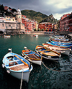 Brightly painted boats line the dock at Vernazza Harbor, Cinque Terre, Liguria, Italy.