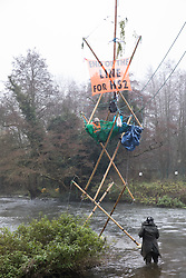 Denham, UK. 7th December, 2020. An activist speaks to Dan Hooper, better known as roads protester Swampy during the 1990s, who is occupying a tripod positioned in the river Colne in order to try to delay bridge building works in connection with the HS2 high-speed rail link. Anti-HS2 activists continue to resist the controversial £106bn rail project from a series of protest camps based along its initial route between London and Birmingham.