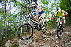 Two Mountainbikers stunt racing forest track