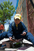 Shoeshine boy with his shoeshine box in the street. La Paz, Bolivia is home to thousands of shoe shine boys who work on the street all over the city. There are so ubiquitous that they represent their own subculture, their trademark being that they hide their faces due to discrimination from the stigma of being a lustrabota. Hormigon Armado is a street paper that functions like the Big Issue, covering issues relating to the shoe shine boys and life on the street, and they sell the paper and keep the money.