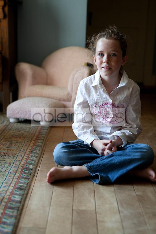 Girl Sitting Cross Legged on Wood Flooring