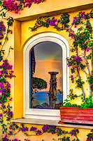 """""""Sunrise reflection of the blue sea in Positano""""…<br /> <br /> After a solemn sunrise morning where I essentially had Positano all to myself and before my strenuous journey down and back up the mountainside, I found my perfect vantage point upon the veranda of my favorite hotel, Albergo California, where I spent photographing the sunset on the first evening in Positano.  Out of the corner of my eye I noticed the orange glow of the sunrise in one of the hotel's windows and captured this reflective image. There was only one occasion that I was really able to pre-plan taking photos at sunrise and that was during the last day of three in Positano.  It takes much planning, logistics, and familiarity to figure the best locations and the proper angles and positions of the sun. My third morning was ideal and fortuitous as it began raining about 10:00 am which gave me perfect clouds for sunrise, finally ending with a very cold wind just in time for sunset.  This image is one of the rare photos of a slumbering Positano in the dewing morning around 6:45 am at the end of May….the beginning of peak tourist season.  By 8:00 am, this tiny seaside village is bustling with tourists and shop owners, and restaurateurs trying to satisfy every need.  All in all, Positano was by far the plushest of all the locations I visited in Italy, and I was blessed to witness everything in full bloom."""