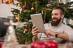Young man using digital tablet against Christmas tree