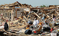 A woman wearing a repirator rests in the rubble of a tornado-destroyed home in Oklahoma City, Oklahoma May 22, 2013.  Rescue workers with sniffer dogs picked through the ruins on Wednesday to ensure no survivors remained buried after a deadly tornado left thousands homeless and trying to salvage what was left of their belongings.  REUTERS/Rick Wilking (UNITED STATES)