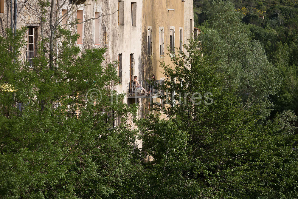 Travellers rest in sunlight on a balcony overlooking French countryside, on 21st May 2017, in Lagrasse, Languedoc-Rousillon, south of France. Lagrasse is listed as one of Frances most beautiful villages and lies on the famous Route 20 wine route in the Basses-Corbieres region dating to the 13th century.