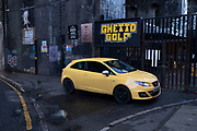 Yellow car parked at Ghetto Golf in the old industrial area and railway arches of Digbeth on 14th December 2020 in Birmingham, United Kingdom. Following the destruction of the Inner Ring Road, Digbeth is now considered a district within Birmingham City Centre, and is the epicentre for arts and graffiti artworks as well as its status as a once-gritty bohemian district known for street art and a young and hip people attending events and creative workshops at the Custard Factory and grungy clubs in former warehouses. As part of the Big City Plan, Digbeth is undergoing a large redevelopment scheme that will regenerate the old industrial buildings into apartments, retail premises, offices and arts facilities. There is still however much industrial activity in the south of the area.