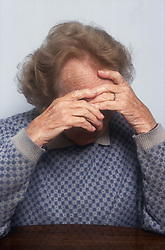Portrait of elderly woman covering face with hands,