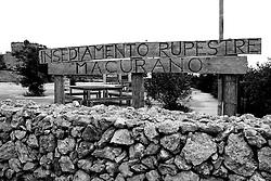 Reportage sul comune di Alessano per il progetto propugliaphoto..Insegna con scritta incisa su assi di legno..Macurano è un villaggio rupestre considerato un luogo di scambio e commercio, simbolo della cultura dell'olio per la presenza ad oggi di alcune tracce nelle grotte e di frantoi funzionanti nella zona. L'insediamento è caratterizzato da una serie di grotte sia naturali che scavate nel calcare, cisterne per la raccolta dell'acqua, sistemi di canalizzazione che scendono da Montesardo, viottoli, scalette e vie più larghe con antiche tracce di carri..Si ritiene che in questo sito, un vero e proprio centro abitato ben organizzato distante circa quattro km dalla costa, i monaci basiliani scappati dall'oriente in seguito alla lotta iconoclasta, trovarono rifugio e si dedicarono all'agricoltura..L'area del villaggio rupestre fu sicuramente sfruttata in epoche successive, lo prova l'esistenza di ben tre masserie di cui una fortificata e i resti di una serie di costruzioni che fanno parte dei numerosi esempi di architettura rurale presenti in questo territorio. .Il complesso masserizio, denominato Macurano, edificato probabilmente nel Cinquecento include la Masseria di Santa Lucia e la cappella di Santo Stefano. La Masseria è dominata dal nucleo originario, ovvero dalla torre cinquecentesca coronata da beccatelli a sostegno del parapetto aggettante del terrazzo sommitale.