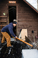 Martin Carney moves the ice blocks with an ice pick into the Rockywold Ice House during the Ice Harvest Wednesday morning with the Rockywold-Deephaven Camp crew.  (Karen Bobotas/for the Laconia Daily Sun)