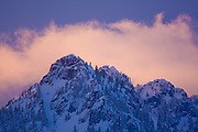 An unnamed peak against pink clouds at sunset near Snoqualmie Pass, Washington.