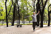 An elderly Chinese man practices martial arts with his cane early morning walk at the Temple of Heaven Park during summer in Beijing, China