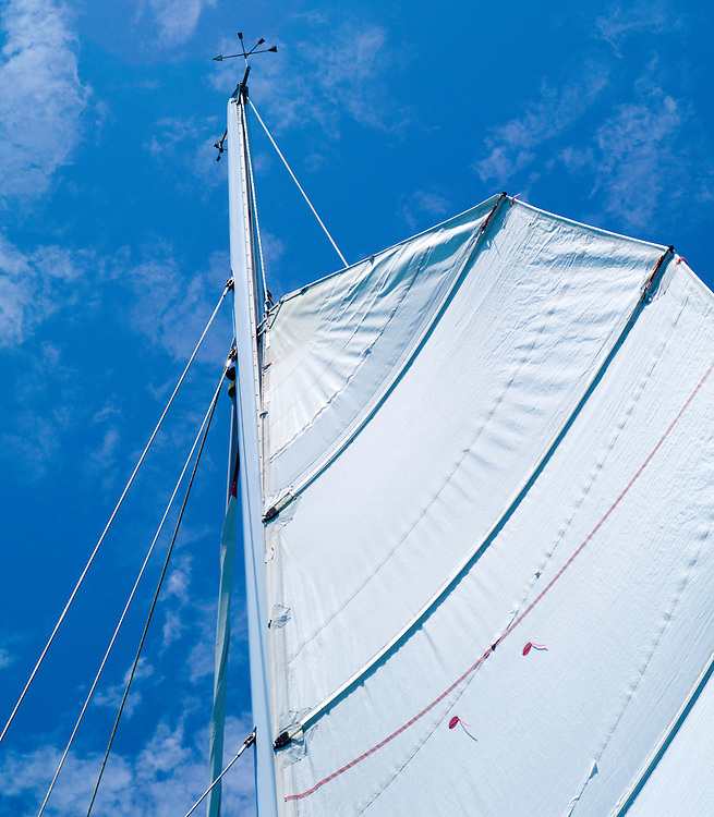 An upward-looking view of the mast and sails of the sailboat Carino, out of Paihia, Bay of Islands, Northland, New Zealand.