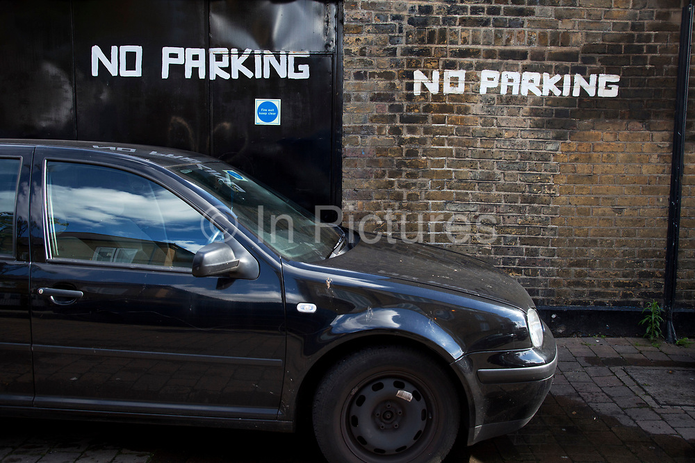 Car parked right in front of a hand painted No Parking sign on a brick wall in a residential street in London.