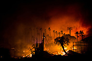 Residential buildings burn along the Pacific Coast Highway during the Woolsey Fire in Malibu, California, Friday, November 9, 2018. The fire burned nearly 97,000 acres and killed three people.