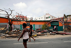 Residents walk in front of the houses destroyed by Irma during the visit of France's President Emmanuel Macron in the French Caribbean islands of St. Martin, Tuesday, Sept. 12, 2017. Macron is in the French-Dutch island of St. Martin, where 10 people were killed on the French side and four on the Dutch. Photo by Christophe Ena/Pool/ABACAPRESS.COM