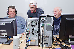 Computer class for people with visual impairments - group of men looking at computer.