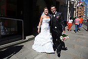 Summertime in London, England, UK. On their wedding day a bride and groom leave the church and head down Fleet Street to their wedding party.