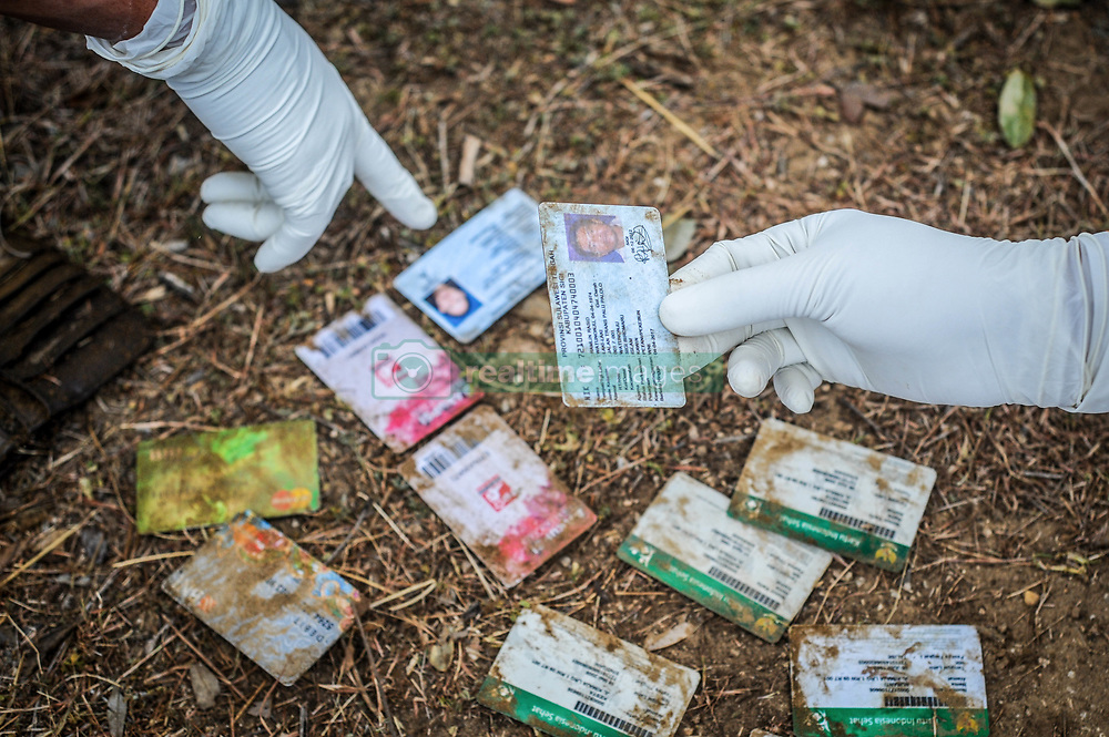 October 4, 2018 - Palu, Central Sulawesi, Indonesia - An government officer collected earthquake and tsunami victims' identities before being mass-buried in Poboya..A deadly earthquake measuring 7.7 magnitude and the tsunami wave caused by it has destroyed the city of Palu and much of the area in Central Sulawesi. According to the officials, death toll from devastating quake and tsunami rises to 1,347, around 800 people in hospitals are seriously injured and some 62,000 people have been displaced in 24 camps around the region. (Credit Image: © Hariandi Hafid/SOPA Images via ZUMA Wire)