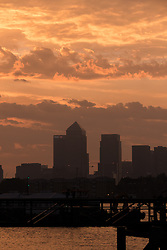 © Licensed to London News Pictures. 25/08/2016. LONDON, UK.  A hazy pink and orange sky is seen behind the Canary Wharf Financial district on the River Thames this morning just after sunrise.  Smog is forecast to sweep across the capital today, creating a potentially toxic haze and smog following the hottest weather of the year yesterday. Photo credit: Vickie Flores/LNP