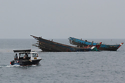 """Indonesian police officers check the debris of destroyed vessels from Malaysia off the coast of Kuala Langsa in Aceh, Indonesia, April 5, 2016. Indonesian authorities sank 23 foreign fishing boats on Tuesday, saying they were """"operating illegally in the archipelago's vast waters in continuation efforts for anti-poaching."""". EXPA Pictures © 2016, PhotoCredit: EXPA/ Photoshot/ Junaidi<br /> <br /> *****ATTENTION - for AUT, SLO, CRO, SRB, BIH, MAZ, SUI only*****"""