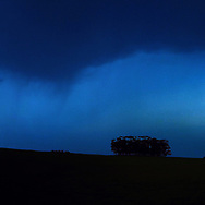 Center triptych panel of a panorama photo of a field swept by blue hues of rain as seen from afar.