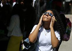 On the first day of school, 11th grader Catherine Geronimo gazes toward the sky on Monday, Aug. 21, 2017 to witness the partial eclipse at Booker T. Washington Senior High School in Miami, Fla. Photo by Carl Juste/Miami Herald/TNS/ABACAPRESS.COM