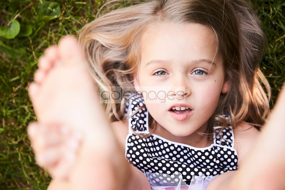 Young Girl Lying on Grass Holding her Feet