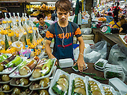 """21 DECEMBER 2015 - BANGKOK, THAILAND:  A man bundles packages sold for Buddhist merit making in Pak Khlong Talat, also called the Flower Market. The market has been a Bangkok landmark for more than 50 years and is the largest wholesale flower market in Bangkok. A recent renovation resulted in many stalls being closed to make room for chain restaurants to attract tourists. Now Bangkok city officials are threatening to evict sidewalk vendors who line the outside of the market. Evicting the sidewalk vendors is a part of a citywide effort to """"clean up"""" Bangkok.      PHOTO BY JACK KURTZ"""