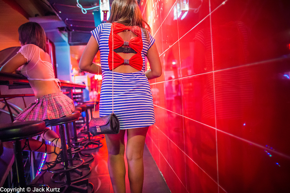 """21 JANUARY 2013 - BANGKOK, THAILAND:  A sex worker leaves a """"short time hotel"""" near the Nana Entertainment Plaza, a red light district in Bangkok. Prostitution in Thailand is technically illegal, although in practice it is tolerated and partly regulated. Prostitution is practiced openly throughout the country. The number of prostitutes is difficult to determine, estimates vary widely. Since the Vietnam War, Thailand has gained international notoriety among travelers from many countries as a sex tourism destination. One estimate published in 2003 placed the trade at US$ 4.3 billion per year or about three percent of the Thai economy. It has been suggested that at least 10% of tourist dollars may be spent on the sex trade. According to a 2001 report by the World Health Organisation: """"There are between 150,000 and 200,000 sex workers (in Thailand).""""  PHOTO BY JACK KURTZ"""