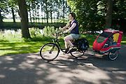 Een moeder fietst met een kind in een aangepaste fietskar bij Bunnik.<br /> <br /> A mother is cycling with a special bicycle trailer nearby Bunnik.