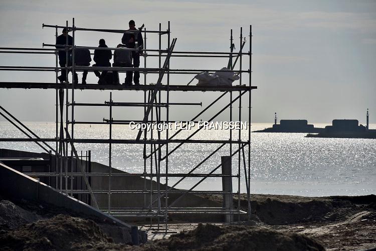 Nederland, Kornwerderzand, 22-2-2018 Jonge bouwvakkers pauzeren, schaften, hebben pauze, schaft, bij het waddencenter, het beleefcentrum de nieuwe afsluitdijk, wadden center . Dit centrum biedt een totaalbeleving over Unesco Werelderfgoed Waddenzee, de Vismigratierivier, het IJsselmeergebied en de Afsluitdijk zelf . Foto: Flip Franssen