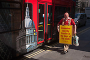 A Christian alongside a London tour bus carries a sandwich board quoting the words of Ecclesiastes 12.1 with the Biblical message that youth should remember their creator, on 8th September 2016, in the City of London, England UK. Walking along Fenchurch Street in the heart of the capitals financial district, founded by the Romans in the first century, the man passes the bus with a large illustration of London landmarks, including St. Pauls Cathedral, and exhibits the quote as a message aimed at the young.