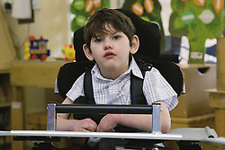 Young boy with physical and leaning disabilities in a lesson,