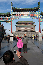 Family taking photographs in front of traditional Chinese gate at Qianmen in central Beijing China