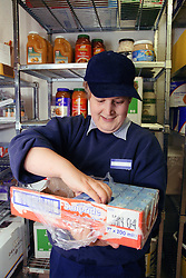 Woman with learning disability emptying food cartons from container in storage area of kitchen,