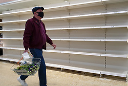 © Licensed to London News Pictures. 03/08/2021. London, UK. A shopper wearing a face covering walks past empty shelves in Sainsbury's, north London. It has been reported that Britain could face a shortage food and drink supplies and these are likely to continue for several months, due to a lack of lorry drivers. Photo credit: Dinendra Haria/LNP
